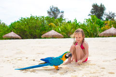 Adorable little girl at beach with colorful parrot Royalty Free Stock Images