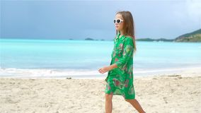 Adorable little girl on the beach. Happy kid enjoy summer vacation. Cute little girl in hat at beach during caribbean vacation stock video