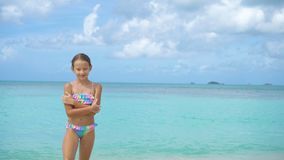 Adorable little girl on the beach. Happy kid enjoy summer vacation. Cute little girl in hat at beach during caribbean vacation stock video footage