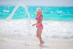 Adorable little girl at beach having a lot of fun in shallow water. Adorable active little girl at beach during summer vacation Royalty Free Stock Image