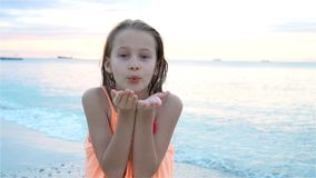 Adorable little girl at beach having a lot of fun at sunset. Happy kid looking at camera and kissing background. Adorable active little girl at beach during stock video footage