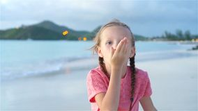 Adorable little girl at beach having a lot of fun at sunset. Happy kid looking at camera and kissing background. Adorable active little girl at beach during stock video