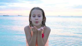 Adorable little girl at beach having a lot of fun at sunset. Happy kid looking at camera and kissing background. Adorable active little girl at beach during stock footage