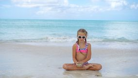 Adorable active little girl sitting on sandy beach. Adorable little girl at beach sitting at water during summer vacation stock footage