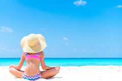 Adorable little girl at beach during summer vacation. Back view of kid on the seashore. Cute little girl at beach during summer vacation Stock Photos