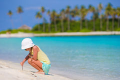 Adorable little girl at beach during summer vacation drawing on sand Royalty Free Stock Photo