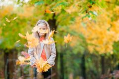 Adorable little girl with autumn leaves in the beautiful park Royalty Free Stock Photo