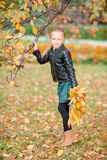 Adorable little girl with yellow leaves bouquet in fall on scooter. Adorable little girl at beautiful autumn day outdoors Stock Photo
