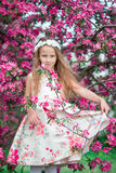 Adorable little girl in beautiful blooming apple garden outdoors Stock Photo