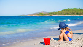Adorable little girl in big blue straw hat at Stock Photography