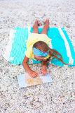 Adorable little girl with big map on beach vacation Stock Photos
