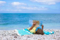 Adorable little girl with big map on tropical Stock Photo