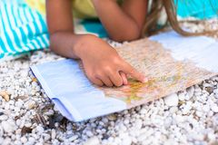 Adorable little girl with big map on tropical Royalty Free Stock Photos