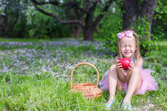 Adorable little girl with big red apple in. Little adorable girls with butterfly wings under blossoming apple tree Stock Photo