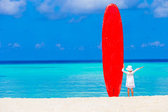 Adorable little girl with big surfboard during Royalty Free Stock Images