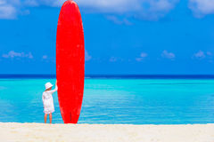Adorable little girl with big surfboard during Royalty Free Stock Photo