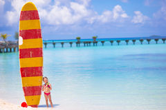 Adorable little girl with big surfboard during Stock Photo