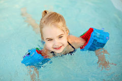 Adorable little girl blonde swimming in the pool with armbands a Royalty Free Stock Images