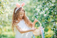 Adorable little girl in blooming apple garden on beautiful spring day. Portrait of beautiful little girl with basket full of eggs and rabbit ears in blooming
