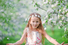 Adorable little girl in blooming apple tree garden on spring day Stock Photos