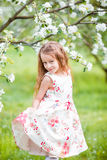 Adorable little girl in blooming apple tree garden on spring day Royalty Free Stock Images