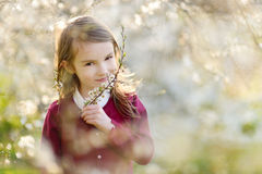 Adorable little girl in blooming cherry garden Stock Photos