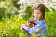 Adorable little girl in blooming cherry garden Stock Photo