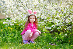 Adorable little girl in blooming cherry garden Stock Photos