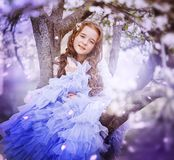 Adorable little girl in blooming cherry tree garden on beautiful spring day. stock photography