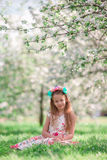 Adorable little girl in blooming cherry tree garden on spring day Stock Photo