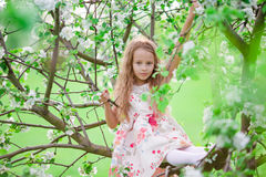 Adorable little girl in blooming cherry tree garden on spring day Royalty Free Stock Image
