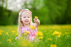 Adorable little girl in blooming dandelion meadow on beautiful spring day Stock Photography