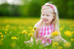 Adorable little girl in blooming dandelion meadow on beautiful spring day Royalty Free Stock Images