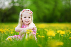 Adorable little girl in blooming dandelion meadow on beautiful spring day Stock Photo