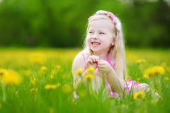 Adorable little girl in blooming dandelion meadow on beautiful spring day Royalty Free Stock Photo