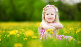 Adorable little girl in blooming dandelion meadow on beautiful spring day Stock Images