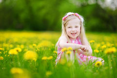 Adorable little girl in blooming dandelion meadow on spring day Stock Photo