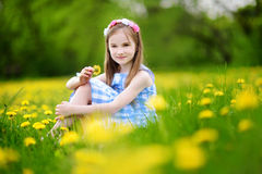 Adorable little girl in blooming dandelion meadow on spring day Royalty Free Stock Photos