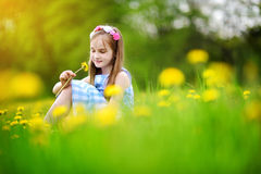 Adorable little girl in blooming dandelion meadow on spring day Royalty Free Stock Image
