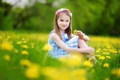 Adorable little girl in blooming dandelion meadow on spring day Stock Photos
