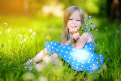 Adorable little girl in blooming meadow on spring day Stock Photos