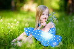 Adorable little girl in blooming meadow on spring day Royalty Free Stock Photos