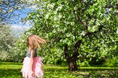 Adorable little girl in blossoming apple garden. Little adorable girls with butterfly wings under blossoming apple tree Royalty Free Stock Photo
