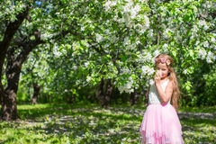 Adorable little girl in blossoming apple orchard. Little adorable girls with butterfly wings under blossoming apple tree Royalty Free Stock Image
