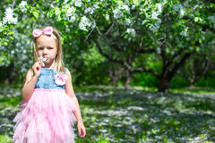 Adorable little girl in blossoming apple orchard. Little adorable girls with butterfly wings under blossoming apple tree Royalty Free Stock Photography