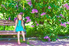 Adorable little girl in blossoming lilac flower Royalty Free Stock Photos