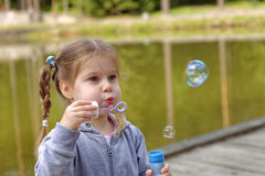 Adorable little girl blowing bubbles in the park Stock Photography