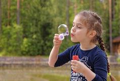 Adorable little girl blowing bubbles in the park Royalty Free Stock Images