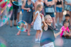 Adorable little girl blowing soap bubbles in european city. Happy kid enjoy summer vacation in Italy Stock Photos
