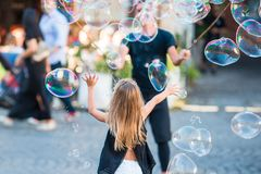 Adorable little girl blowing soap bubbles in Trastevere in Rome, Italy. Adorable little girl blowing soap bubbles in Trastevere in Rome. Happy kid enjoy summer royalty free stock photos